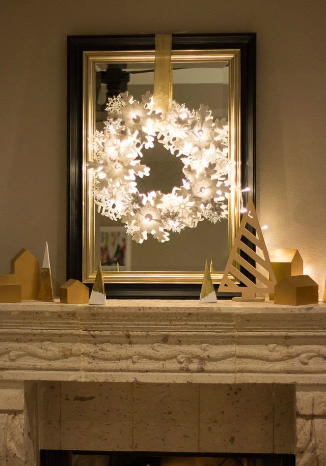Glowing snowflake wreath over fireplace mantel