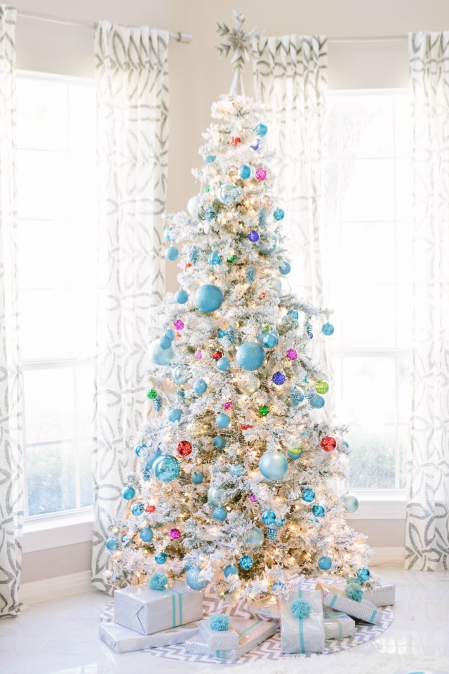 Flocked Christmas tree covered with jewel-toned ornaments