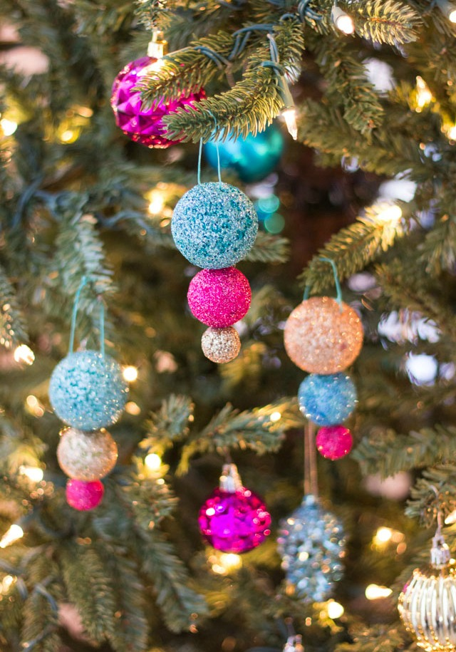 Glitter ball ornaments hanging from a Christmas tree