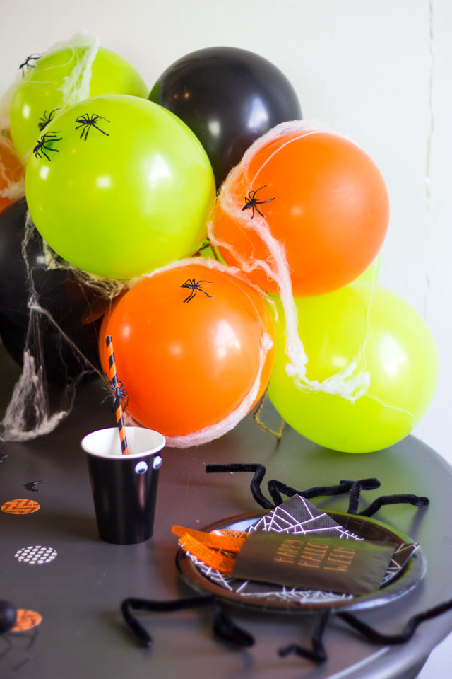 Cover balloons with spiders and spider webs for spooky Halloween decor!