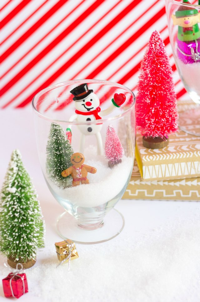 Fill glass jars with faux snow and mini Christmas toys for these sweet Christmas terrariums!
