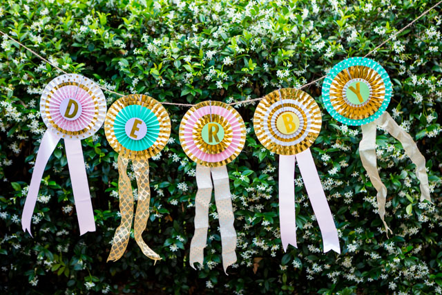 Turn paper party fans into a DIY ribbon banner for your Kentucky Derby party!