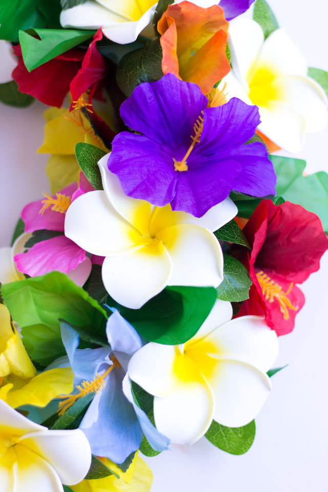 Make this DIY tropical flower wreath with faux hibiscus and plumeria!