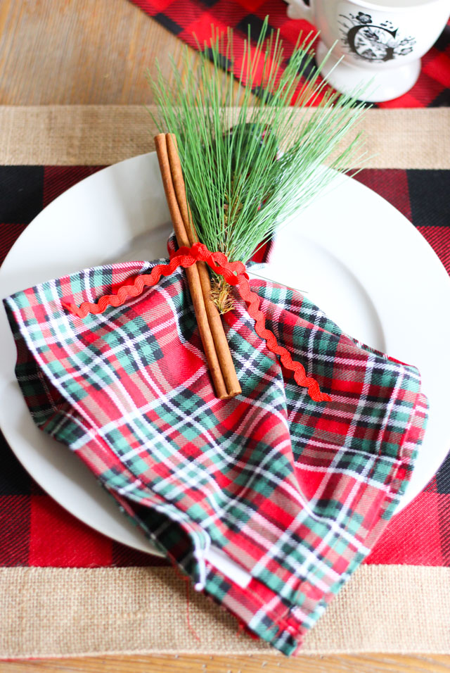 Simple and sweet Christmas place setting idea - tie a cinnamon stick and evergreen sprig around a napkin!