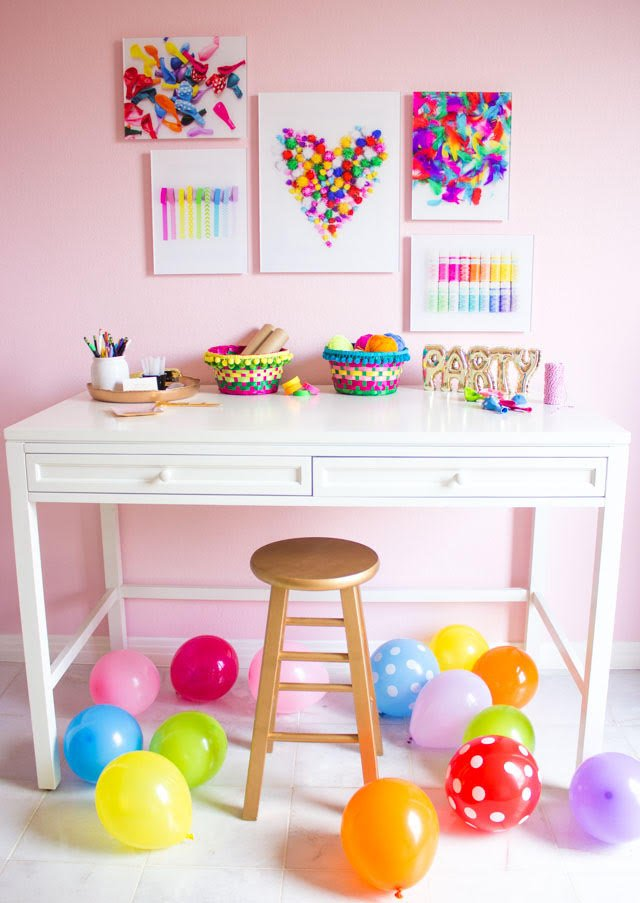 Pink craft room with colorful craft supply wall art and balloons