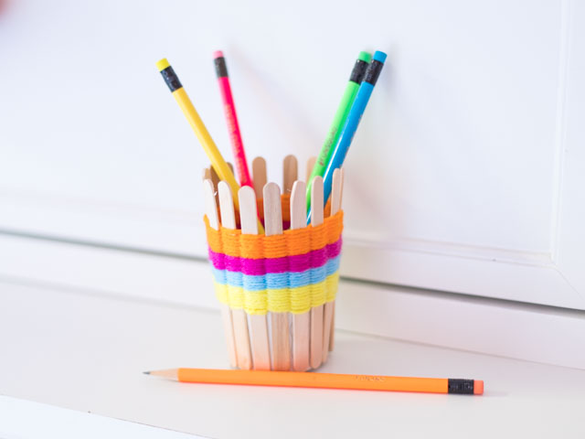 Use popsicle sticks and yarn to make these pretty woven pencil cups. Such a fun kids craft! #yarncrafts #kidscrafts #popsiclestickcrafts #popsiclestickweaving #kidsweaving