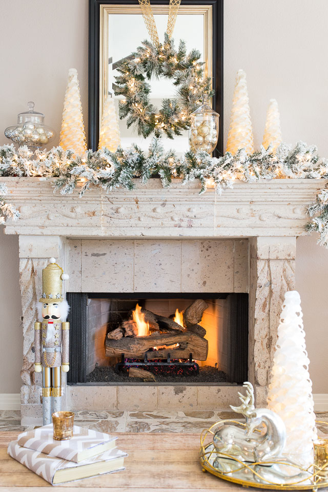 Silver and gold Christmas decorations on fireplace mantel