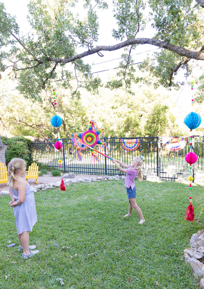 Colorful piñata and tassels hung from trees
