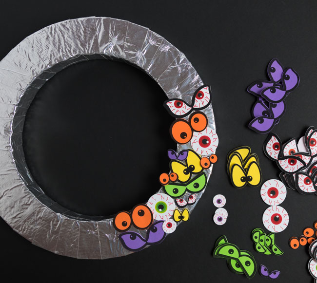 Adding eyeball stickers to wreath form