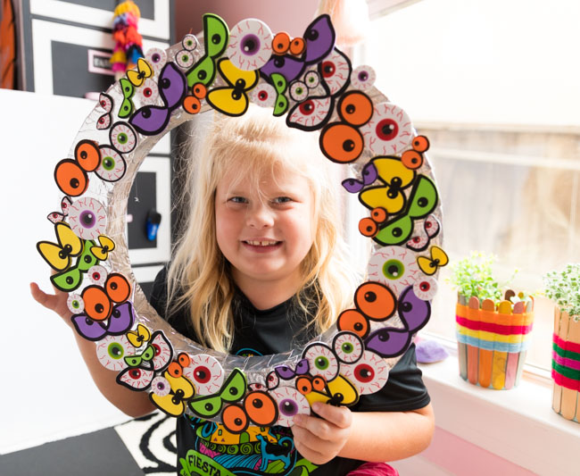 Child holding Halloween eyeball wreath
