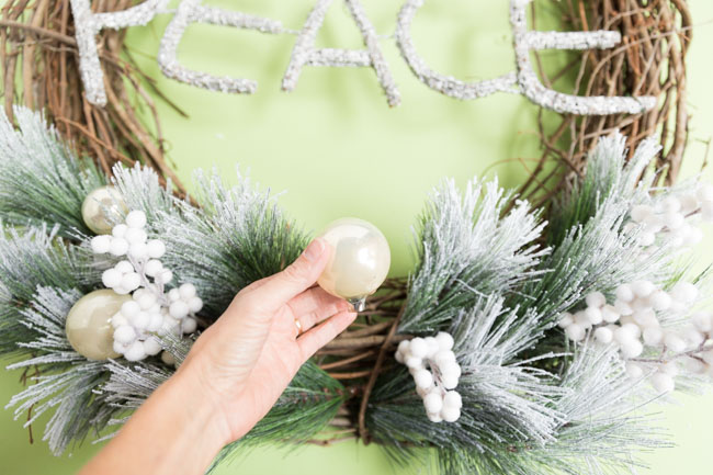 Adding ornaments to a Christmas wreath