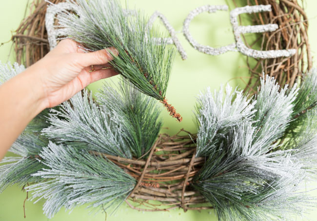 Adding greenery picks to a grapevine wreath