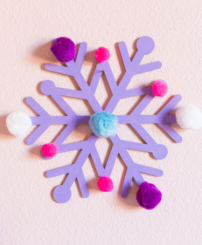 Giant wood snowflake with paint and pom-poms