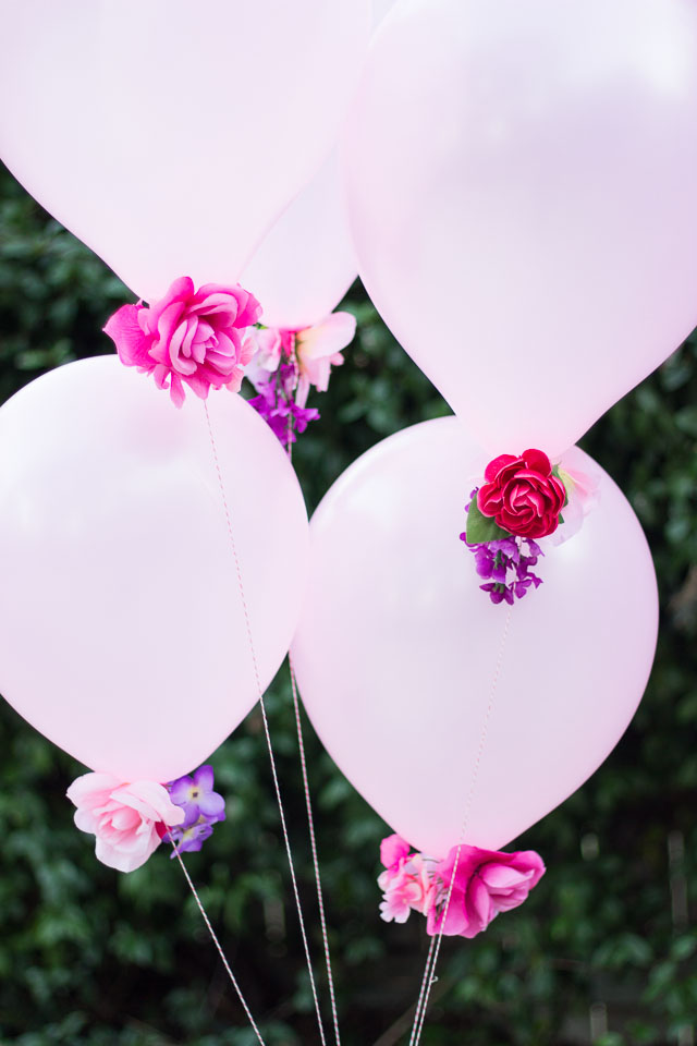 Add artificial flowers to the base of balloons