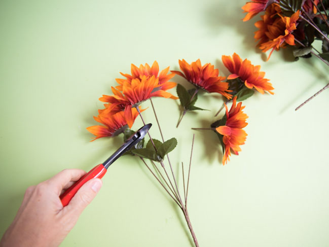 Clipping artificial flowers from their stems with wire cutters