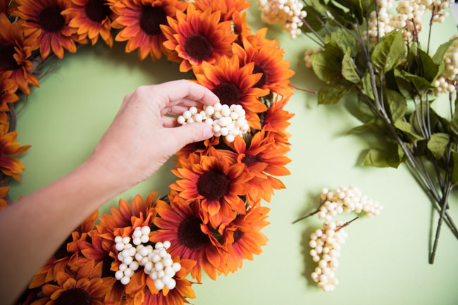 Adding berries to fall wreath