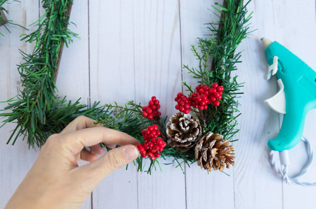 Making a DIY Christmas picture frame with pinecones and berries